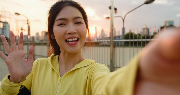 Attractive young asia athlete influencer lady recording video vlog live streaming on phone upload in social media while exercises in urban city. sportwoman wearing sports clothes on street in morning. Free Photo