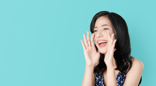Attractive young asian woman announcing with hands to the mouth and telling a secret. Premium Photo