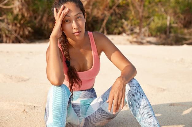 Tシャツとレギンスに身を包んだ魅力的な若いアジアの女性は、砂浜で運動した後休憩します 無料写真