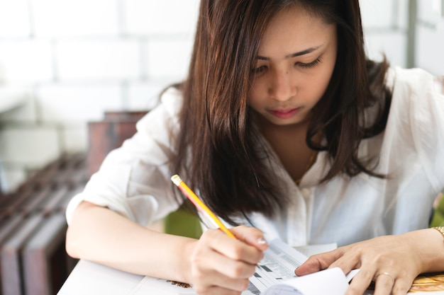 Attractive young asian woman used pencil to writing on papers in cafe. Premium Photo