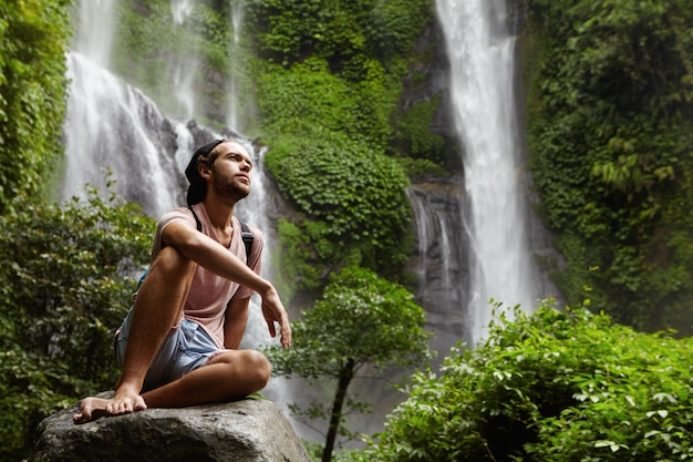Attractive young bearded adventurer wearing no shoes having break on big rock while trekking alone in tropical forest. stylish hiker relaxing outdoors in jungle with amazing waterfall Free Photo