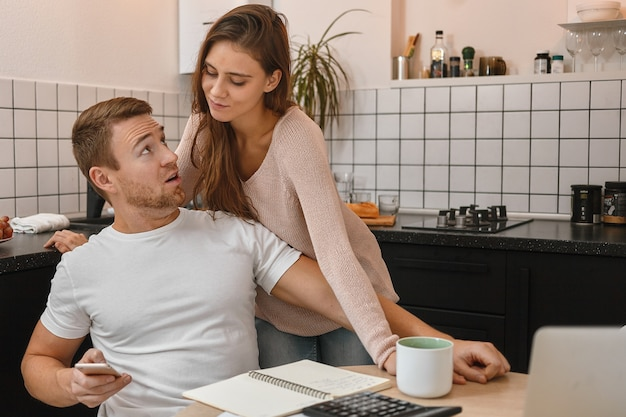 서류, 노트북, 계산기와 함께 테이블에 부엌에 앉아, 스마트 폰을 들고, 의심스러운 아내에게 Sms를 거부하는 흰색 티셔츠에 매력적인 젊은 수염 난된 남자. 사람과 기술 무료 사진
