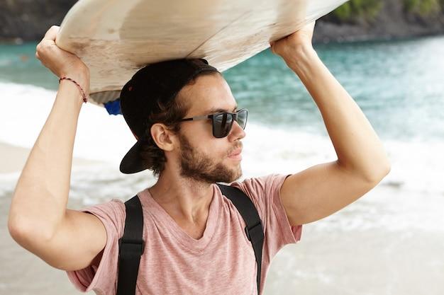 Привлекательный молодой бородатый мужчина в солнцезащитных очках, несущих бодиборд над головой и смотрящий на океан Бесплатные Фотографии