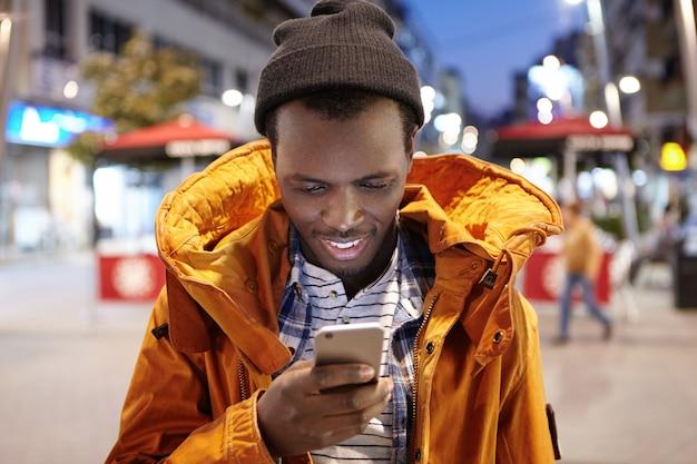 夜の街の環境に立っている彼の携帯電話にテキストメッセージを入力する冬の衣類の魅力的な若い黒ヨーロッパ人。 smsを読んでうれしそうな浅黒い男性 無料写真