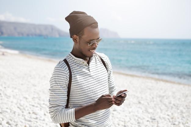 Привлекательный молодой черный улыбающийся мужчина путешественник в модных тонах с помощью смартфона, отправка электронной почты своим родственникам, выглядит счастливым во время прогулки по океану в одиночку. люди, образ жизни и путешествия Бесплатные Фотографии