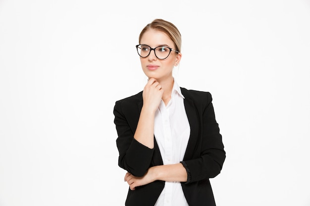 Attractive young blonde business woman in eyeglasses holding hand near chin and looking away over white Free Photo