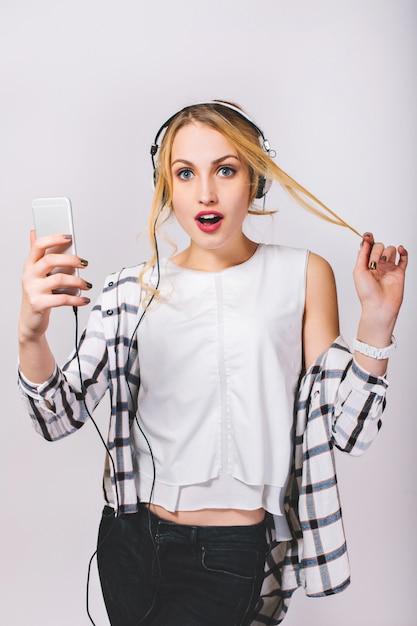 Привлекательная молодая блондинка женщина с большими белыми наушниками, слушать музыку на смартфоне. милая девушка, касаясь ее волос. удивил большие голубые глаза, открыл рот. изолированный. Бесплатные Фотографии