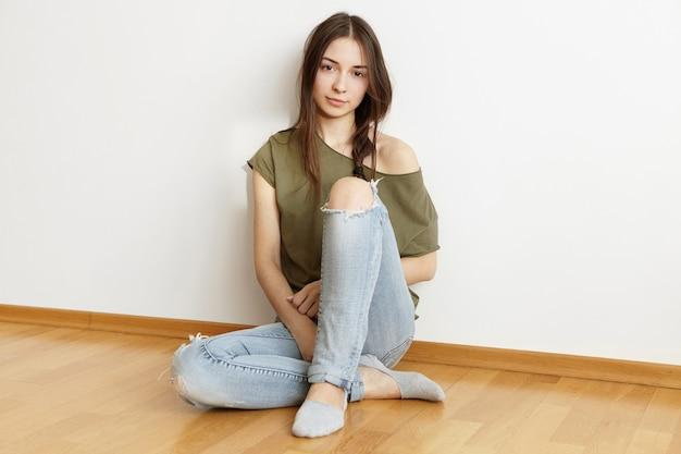 トレンディなボロボロになったジーンズとオープンショルダーのトップを着て魅力的な若いブルネットの女性 無料写真