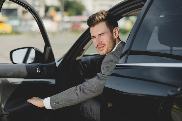 An attractive young businessman looking out from car Free Photo