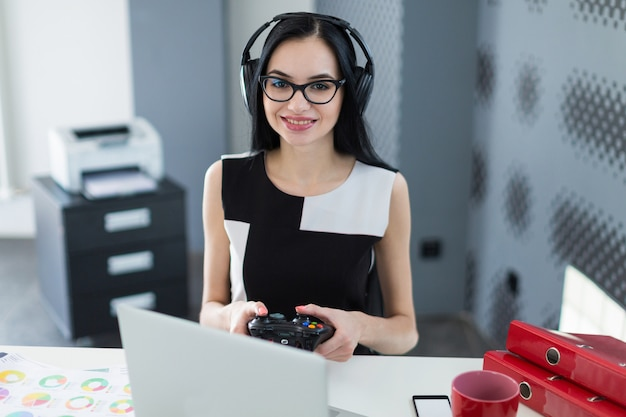 Attractive young businesswoman in black dress, headphones and glasses sit at the table and play on laptop Premium Photo