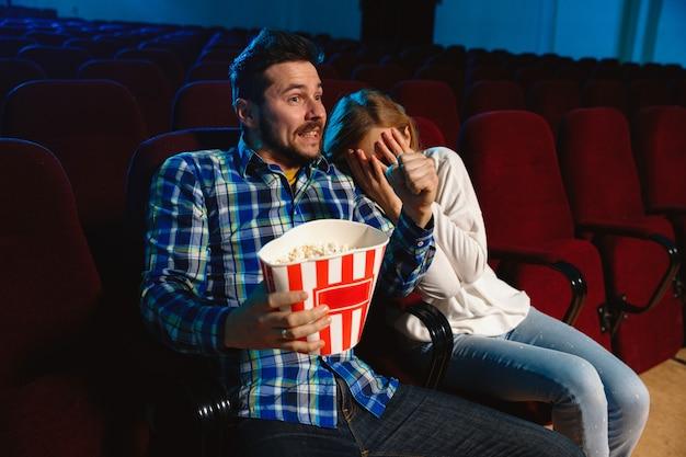 영화 극장, 집 또는 영화관에서 영화를보고 매력적인 젊은 백인 부부. 표현력이 풍부하고 놀랍고 감정적으로 보입니다. 혼자 앉아서 즐겁게 지내기. 관계, 사랑, 가족, 주말 시간. 무료 사진