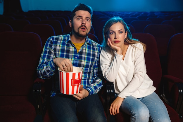 Attractive young caucasian couple watching a film at a movie theater, house or cinema. Free Photo