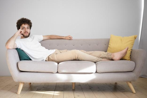 波状の髪型と厚いあごひげを生やした魅力的な若い白人男性は、仕事の後に自宅で休んで、独身のアパートのソファに裸足で横たわり、物思いにふける思慮深い表情をしています。 無料写真