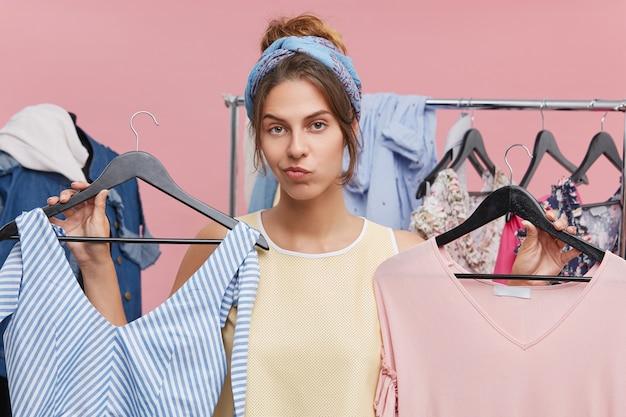 魅力的な若い白人女性のお客様は、2つの服でハンガーを保持しているので、どちらがぴったり合っているかを判断する際に疑問を感じます。ショッピング、選択、ジレンマ、購入、購入 無料写真