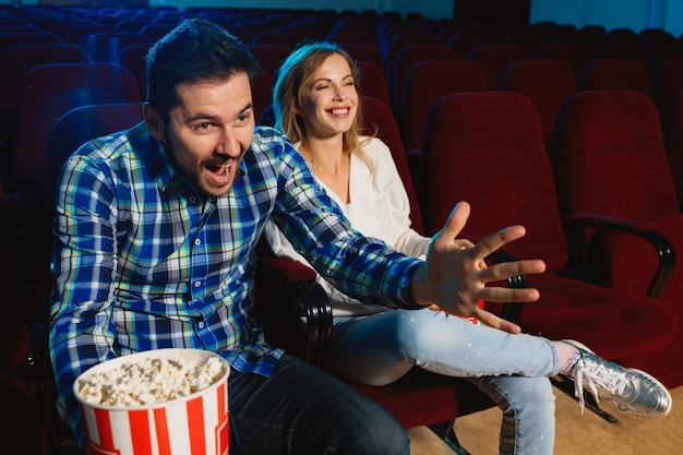 Attractive young couple watching a film at a movie theater Free Photo