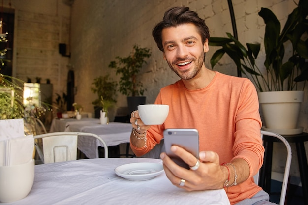 Attractive young dark haired man in sweater posing over cafe interior, holding srartphone in hand and looking cheerfully, having cup of coffee Free Photo