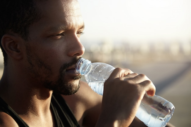 Attractive young dark skinned sportsman with short beard drinking water from bottle looking far away with thoughtful face expression, dressed in black sleeveless shirt, relaxing after morning run Free Photo