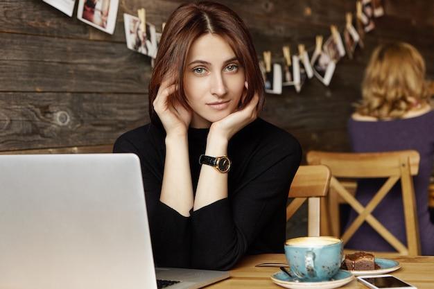 魅力的な若いヨーロッパの女性のコラムニストはマグカップ、デザート、携帯電話、ラップトップコンピューターのカフェのテーブルに座っている黒いドレスを着て服を着て、オンライン女性誌の新しい記事に取り組んでいます 無料写真