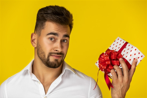Attractive young european guy in white shirt is holding one present Free Photo