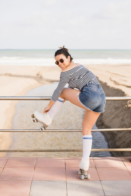 An attractive young female skater tying the roller skate lace at beach Free Photo