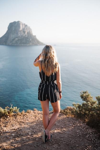 昼間の美しい海のそばの崖の上に立っている魅力的な若い女性 無料写真