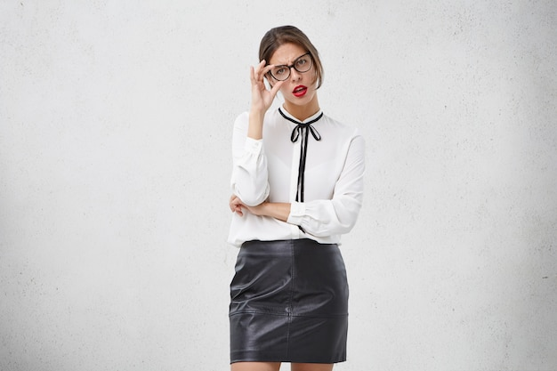 魅力的な若い女性は眼鏡とフォーマルな服を着ています 無料写真