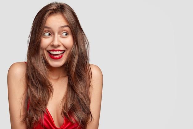Привлекательная молодая женщина с длинными темными прямыми волосами, со счастливым выражением лица, красными губами, небрежно одетая, стоит у белой стены Бесплатные Фотографии