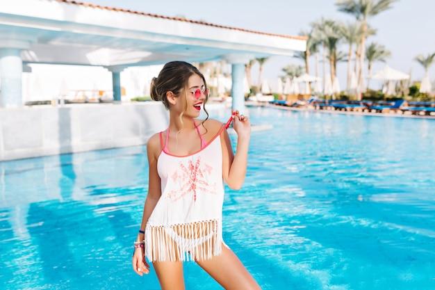 Attraente giovane ragazza in abito da spiaggia in piedi davanti alla piscina all'aperto con palme sullo sfondo e guardando lontano Foto Gratuite