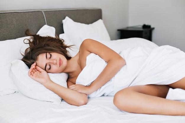 Привлекательная молодая девушка, спать на белой кровати в современной квартире утром. Бесплатные Фотографии