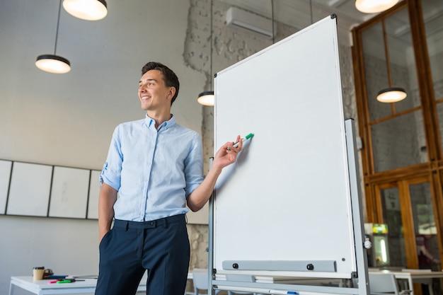Привлекательный молодой красивый улыбающийся человек, стоящий на пустой белой доске с маркером Бесплатные Фотографии