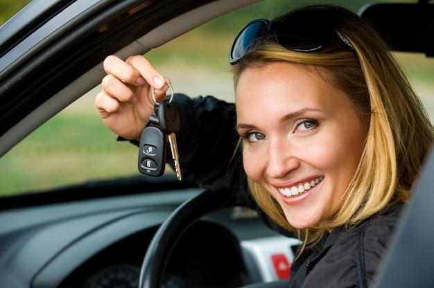 La giovane donna felice attraente mostra le chiavi dalla nuova automobile - all'aperto Foto Gratuite