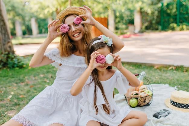 Attraente giovane donna in cappello di paglia retrò scherzando con la figlia e giocando con i biscotti colorati. due sorelle sveglie che hanno picnic nel parco estivo e ridendo. Foto Gratuite