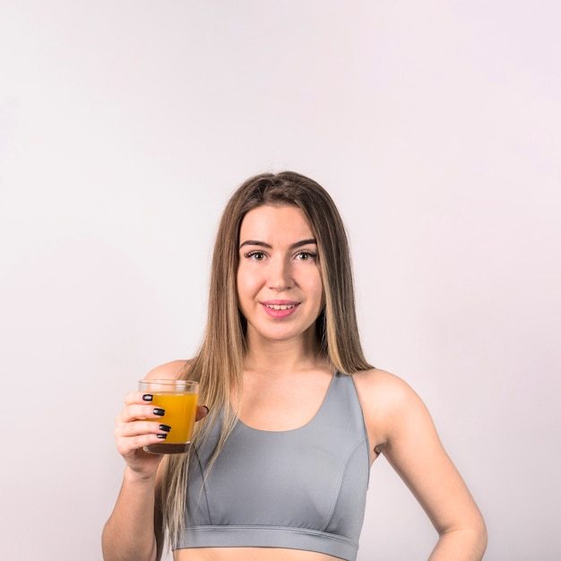 Attractive young lady in sportswear with glass of juice Free Photo