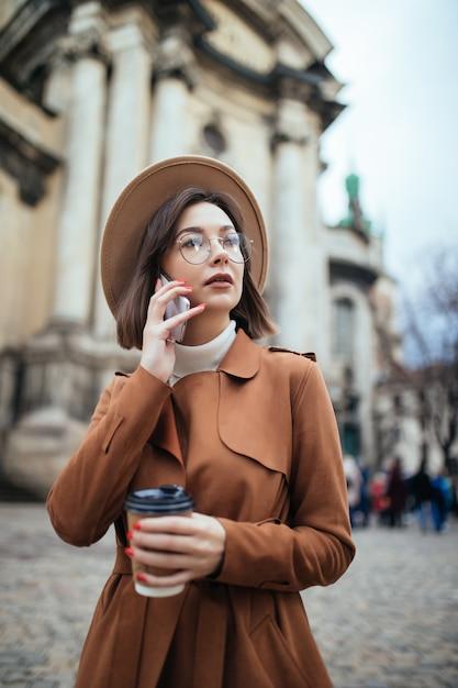 寒い秋の日に野外を歩いている携帯電話で話している魅力的な若い女性 無料写真