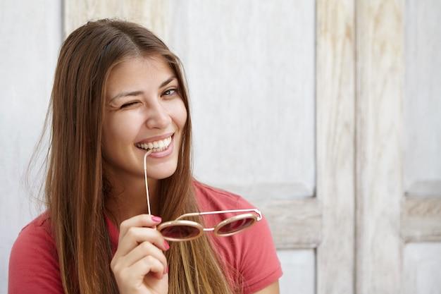 Привлекательная молодая дама с красивыми волосами флиртует, подмигивает, держит в руках солнцезащитные очки и с игривой улыбкой кусает кончик виска. Бесплатные Фотографии