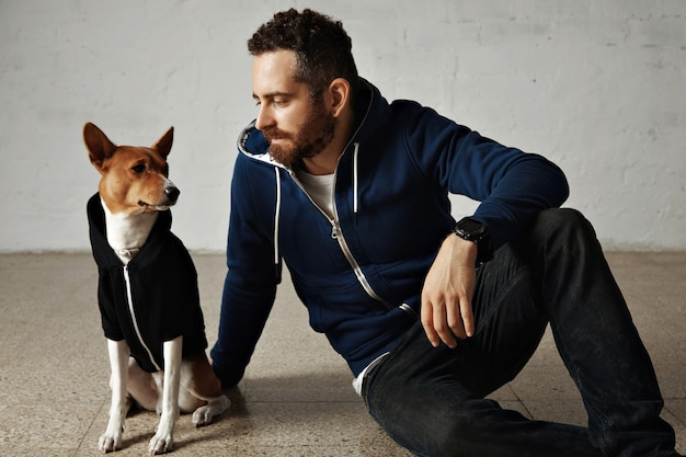 An attractive young man and his bassenji dog wearing matching hoodies sit on the floor next to white wall Free Photo