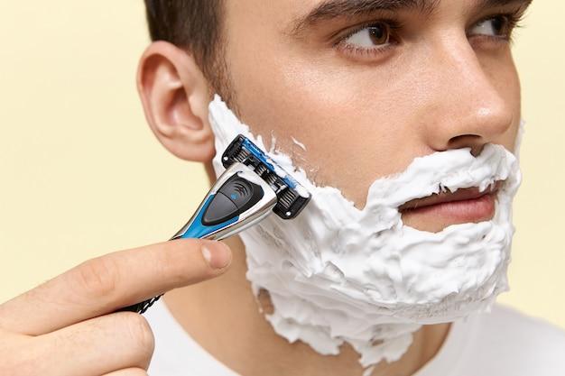 거품을 사용하여 얼굴을 면도하기 위해 일회용 면도기를 들고 일하기 전에 면도하는 매력적인 젊은 남자 무료 사진