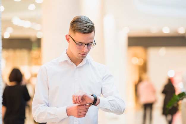 An attractive young man in white shirt looking his wrist watch; checking the time Free Photo