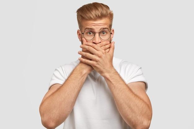トレンディなヘアカットを持つ魅力的な若い男は、口を覆い、無言である 無料写真