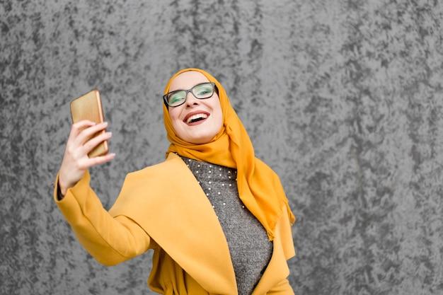 Привлекательная молодая мусульманская женщина, принимая селфи Бесплатные Фотографии