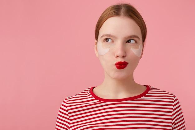 Привлекательная молодая таинственная рыжеволосая женщина с красными губами и пятнами под глазами, одетая в красную полосатую футболку, смотрит в левую сторону, что-то замышляет, стоит на розовом фоне. Бесплатные Фотографии