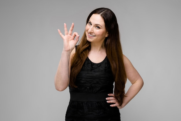 Attractive young positive brunette caucasian smiling woman in black dress showing ok sign isolated on gray Premium Photo