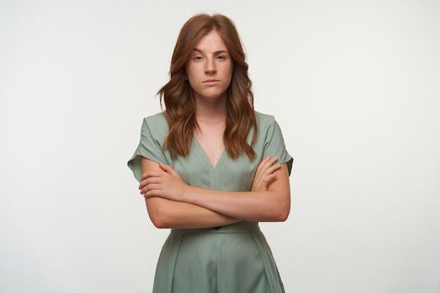 Attraente giovane donna rossa in piedi con le braccia incrociate sul petto, alzando le sopracciglia e avendo uno sguardo incredulo Foto Gratuite