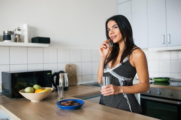 Attraente giovane donna sorridente magra divertirsi in cucina al mattino facendo colazione vestita in abito pigiama mangiare biscotti bere latte, stile di vita sano Foto Gratuite