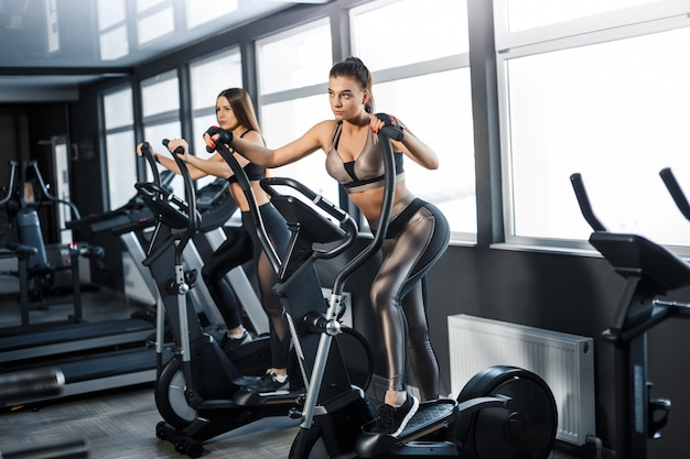 Attractive young sports woman is working out in gym. doing cardio training on treadmill. running on treadmill Premium Photo