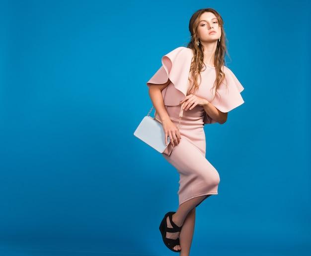 유행 핸드백을 들고 핑크 럭셔리 드레스, 여름 패션 트렌드, 세련된 스타일, 블루 스튜디오 배경에 매력적인 젊은 세련된 섹시한 여자 무료 사진