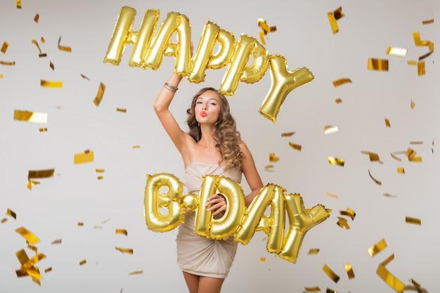 魅力的な若いスタイリッシュな女性を祝って、気球お誕生日おめでとう文字、金色の紙吹雪を飛んで、笑って幸せ、分離、パーティードレスを着て 無料写真