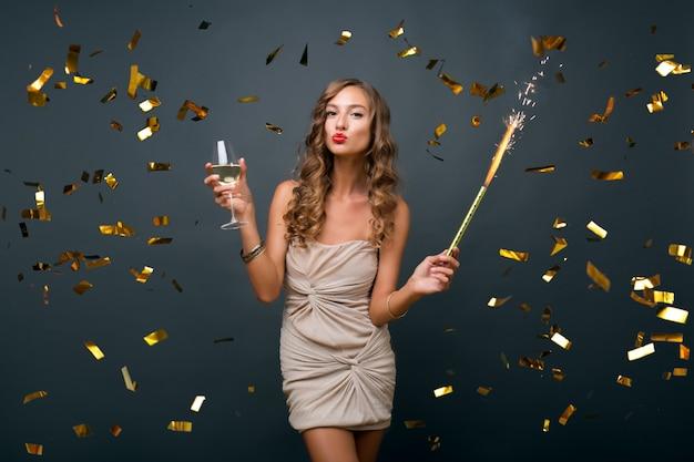 Привлекательная молодая стильная женщина празднует новый год, пьет шампанское, летит золотое конфетти, улыбается счастливым, изолированным, в вечернем платье Бесплатные Фотографии