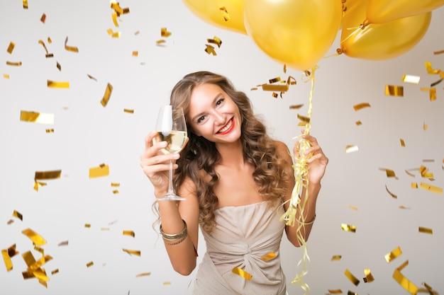 Привлекательная молодая стильная женщина празднует новый год, пьет шампанское, держит воздушные шары, летит золотое конфетти, улыбается счастливым, белым, изолированным, в праздничном платье Бесплатные Фотографии