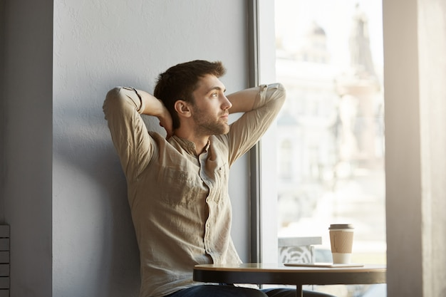 Attractive young unshaven guy sitting in cafe, drinking coffee, looking at window with hands behind his head, exhausted after business meeting Free Photo